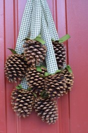 a fall decoration of pinecones hanging on gingham ribbons is a nice and simple idea that can be easily and fast DIYed