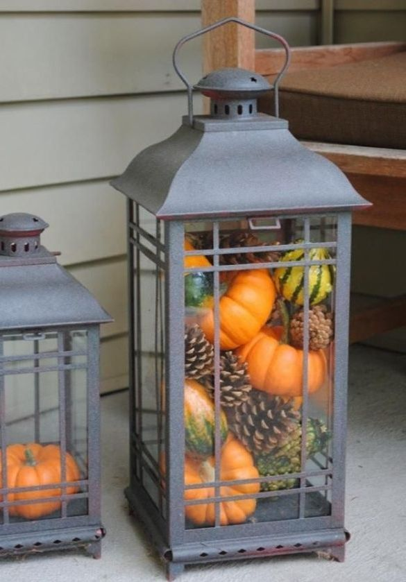 a large candle lantern filled with pinecones, gourds and pumpkins is a lovely idea to decorate your front porch