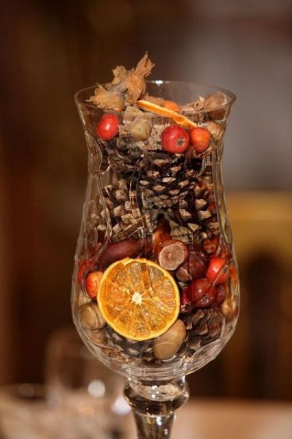 a tall glass filled with faux berries, nuts, pinecones and citrus slices is a cool fall decoration or a centerpiece