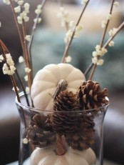 a large vase with white pumpkins and pinecones, with blooming branches for chic and neutral fall decor