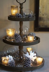 a wooden stand with snowy pinecones, acorns, nuts, candle lanterns and glass bubbles for chic fall decor