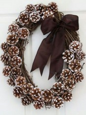a vine wreath with snowy pinecones and a brown ribbon bow is a stylish and elegant idea for both fall and winter