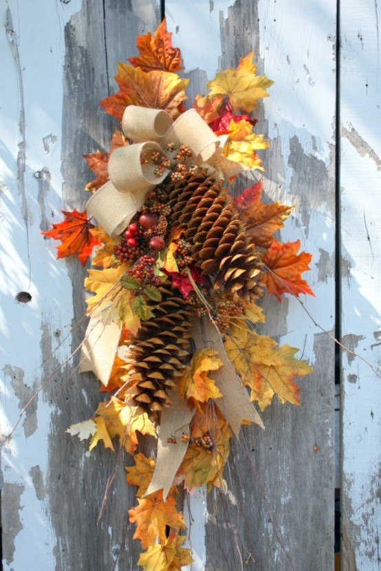 a fall posie with fall leaves, pinecones, a burlap bow is a fun and cool fall decoration to hang anywhere