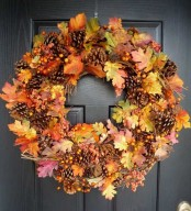 a bright fall wreath of pinecones, bold fall leaves berries is a stylish and timeless front door decoration