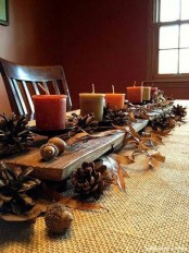 a fall centerpiece of pinecones, fall leaves, nuts and acorns and fall-colored candles is a very natural autumn decoration