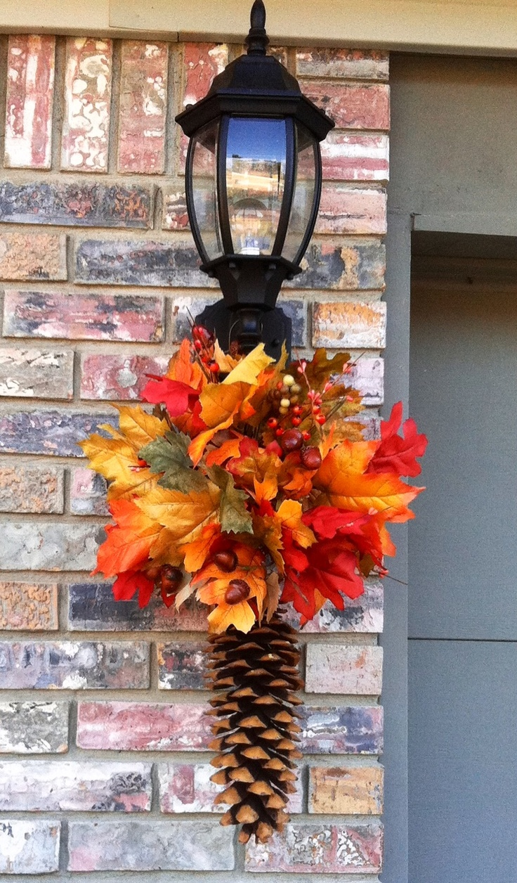 a bright fall decoration of a pinecone, bold faux leaves and berries can accent your front door or any other space