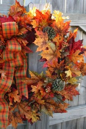 a bold fall wreath of faux leaves, berries, pinecones and accented with a bright plaid ribbon bow for your front door