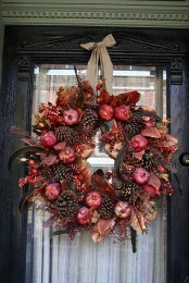 a moody fall wreath of pinecones, faux berries, pomegranates, grasses, foliage and feathers for a boho feel