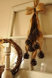a cool and easy woodland fall decoration of a gold bow with many pinecones hanging down