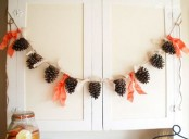 a fall pinecone garland with bright orange fabric touches will be a nice decoration for your space in the fall