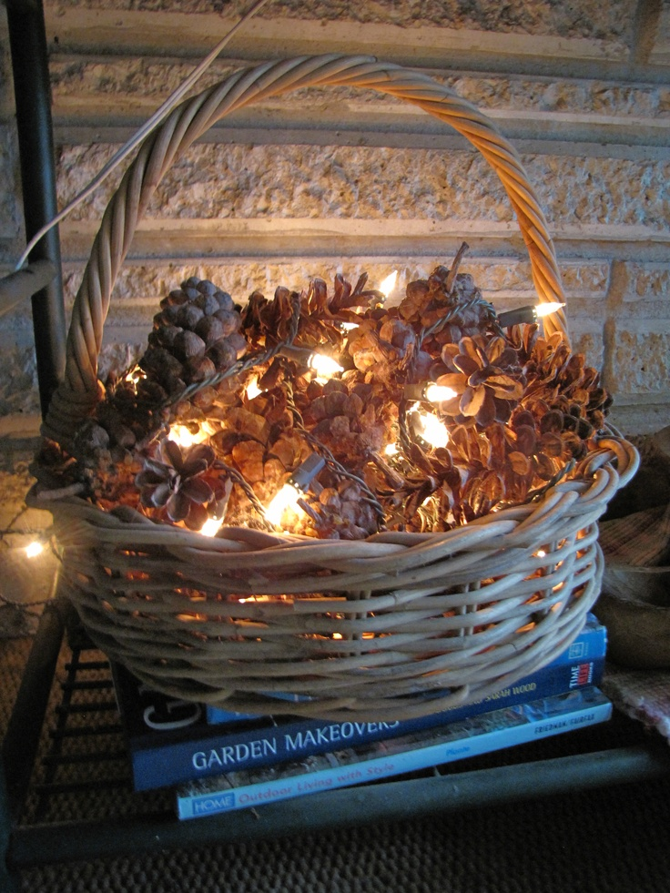 a basket filled with pinecones and lights is a cute and very simple fall or winter decoration