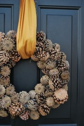 a large pinecone wreath with mustard ribbon is an all-natural and very cool decoration for your front door in the fall