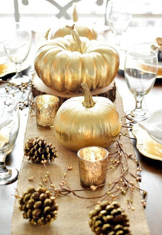 fall table decor wuth a burlap table runner, gilded pinecones, candles in gold mercury glass candleholders and gilded pumpkins for a fall party or Thanksgiving