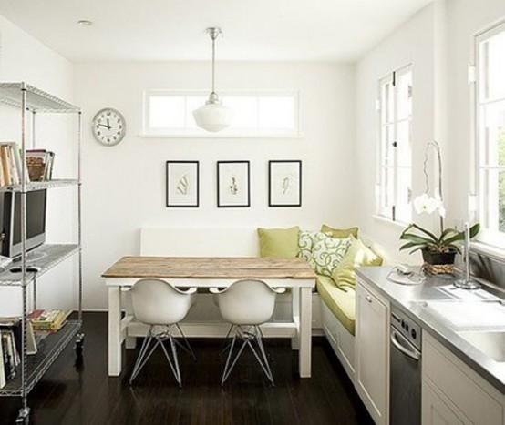 a small contemporary kitchen in white, with an L-shaped bench, a wooden top table, a large open storage unit