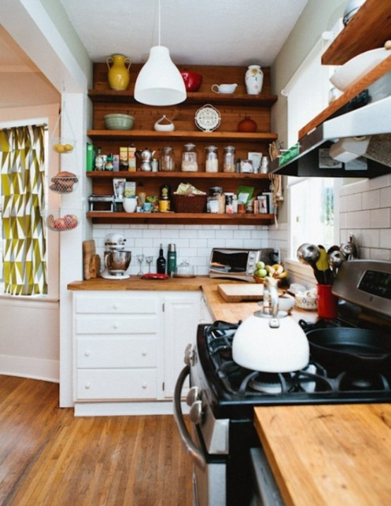 a small modern kitchen done in white and rich stained wood, with lots of open shelves and white tiles