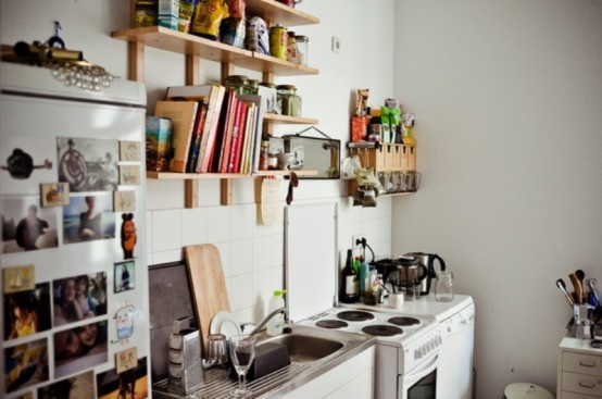 a small contemporary kitchen in white, with light-stained wooden shelves and lots of personal photos