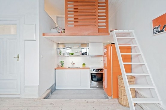a bright small kitchen with white cabinets, a bright orange fridge, orange countertops and lime touches