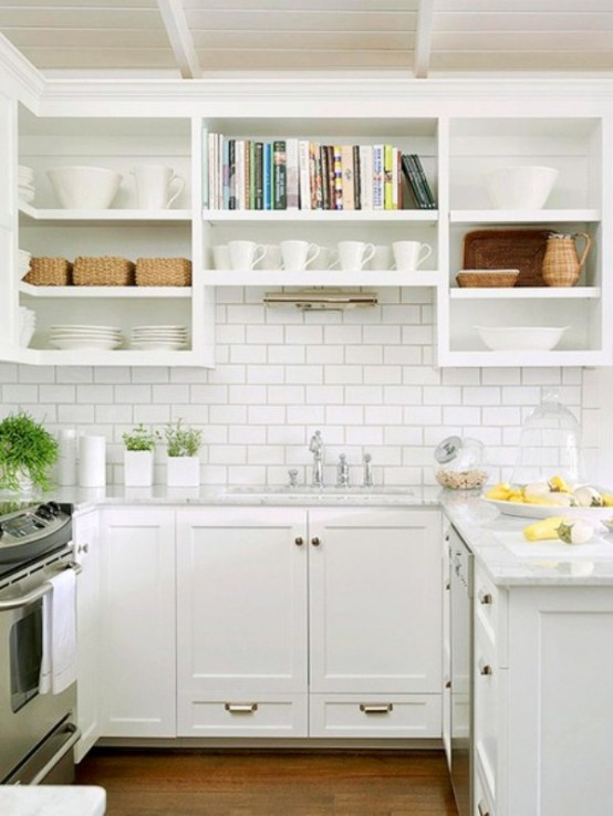 a small yet stylish farmhouse kitchen in white, with gold hardware, white subway tiles and open shelves plus drawers for storage