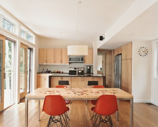 a small contemporary kitchen done with light stained wooden cabinets, a table and rust chairs
