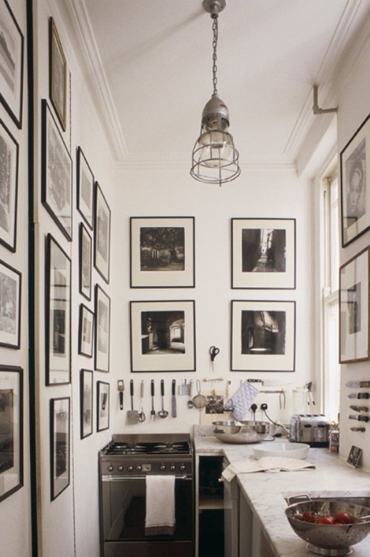 a small monochromatic kitchen done with neutral cabinets and countertops, black and white photos on the walls and a pendant lamp