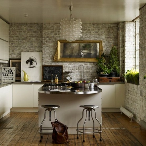 a small glam kitchen with brick walls, white cabinets and metal countertops, a frosted glass chandelier