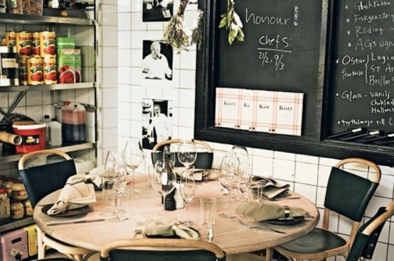 a small industrial mela space with a wooden round table, leather chairs, open shelving units and chalkboards