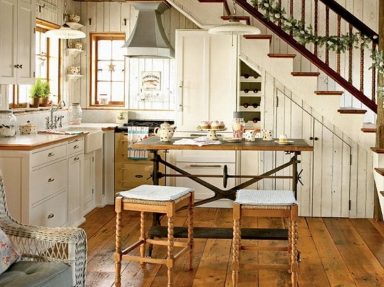 a small farmhouse kitchen with white cabinets, light stained countertops, a vintage table and carved stools, pendant lamps