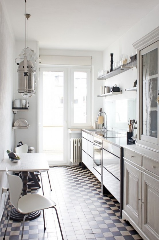 a vintage Scandinavian kitchen in white with open shelving and cabinets, a rustic space with chairs and a carved wooden table plus a mosaic floor