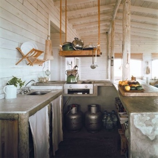 a small rustic meets industrial kitchen with concrete countertops, metal churns and suspended wooden shelves