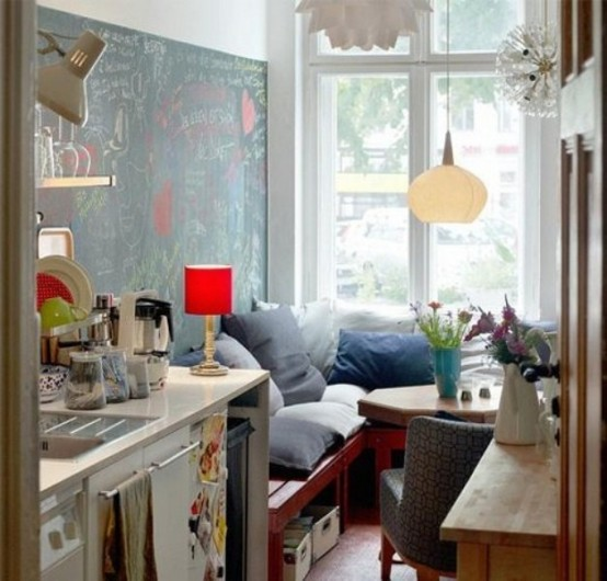 a tiny eclectic kitchen with some cabinets and a cozy nook by the window with a hexagon table