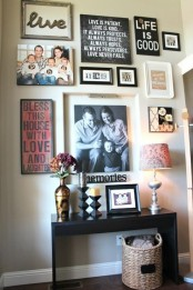 an eclectic gallery wall with various photos, signs and artworks in various frames and with additional light