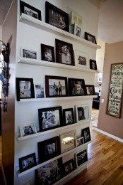 an oversized gallery wall with white ledges and black and white photos in mismatching black and white frames is a timeless idea
