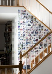 a staircase side fully covered with colorful family photos without frames is a stylish idea to use usually an unused surface