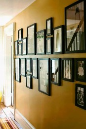 an elegant vintage gallery wall of photos in matching black frames hanging in two horizontal rows looks chic