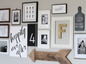 a gallery wall in black and white, with mismatching frames, signs, numbers and a wooden arrow is creative and fun
