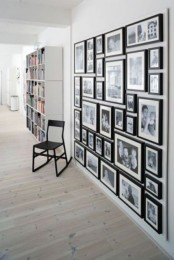 a large black and white gallery wall with black and white family photos in matching black frames is always a stylish idea