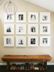 a stylish gallery wall with black and white photos in matching white frames over the bench form a cool composition