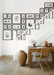 a large gallery wall over the staircase done with black and white photos in black frames is a chic idea for home decor
