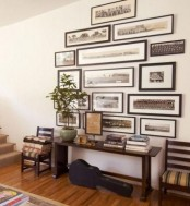 a large gallery wall with black and white photos in black frames is a cool decoration for a modern entryway
