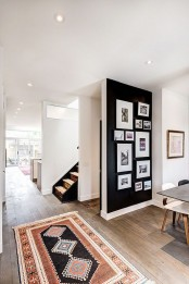 a catchy gallery wall with black and white and color photos in matching black frames that make it cohesive