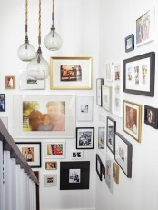 an eclectic gallery wall with color and black and white photos in mismatching frames will make going up and down more interesting