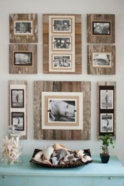 a rustic gallery wall with weathered wood planks and black and white photos attached to burlap and black fabric