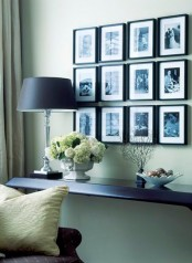 a stylish black and white gallery wall with photos in black frames is always a good idea to decorate and personalize your space a bit