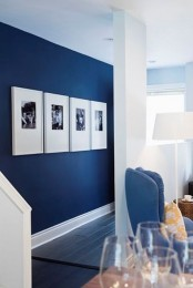 a minimalist gallery wall with black and white photos in white frames – just one row full of style