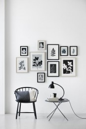 a chic gallery wall with black and white photos in black and white frames placed with a bit of chaos