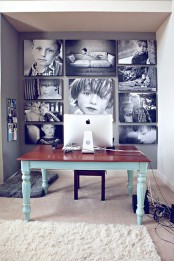 a home office with a black and white gallery wall with unframed pics that cover the whole wall and make a statement