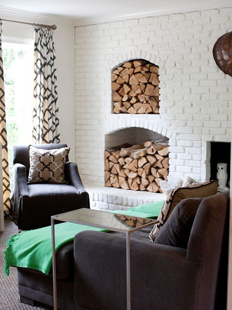 a white brick wall with a non-working fireplace and a couple of matching niches that hold firewood matches the interior and makes it more rustic and cozier