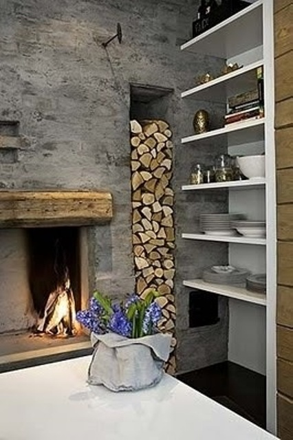 an open hearth with a wooden frame and a niche for firewood next to it, right in the wall is a very cozy and rustic idea to pull off