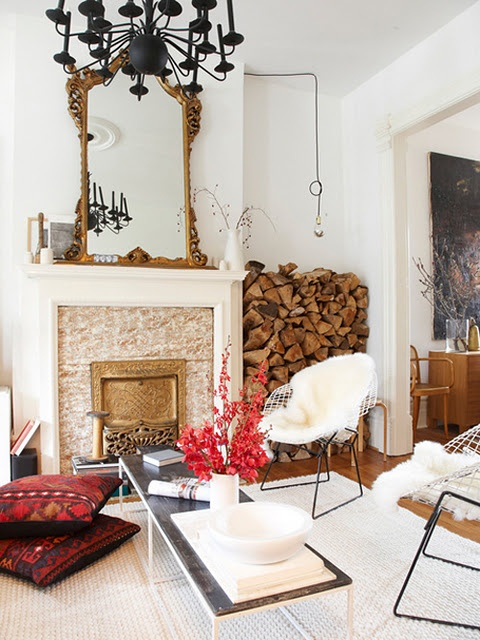 an eclectic space with a non-working and very refined fireplace and firewood stored between it and the wall for maximal coziness