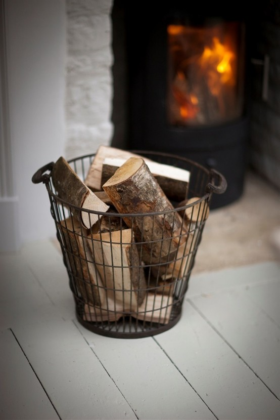a wire basket with firewood is a cool idea to store it adding coziness and a vintage feel to the space